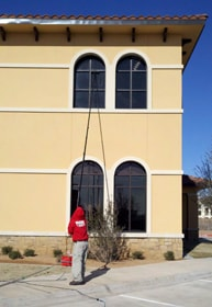 Cleaning second story windows with a pole