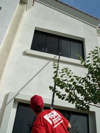 Cleaning exterior window on second story with a pole