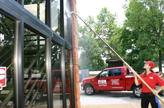 Cleaning exterior windows of a commercial building with a pole