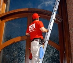 Cleaning residential windows with a ladder