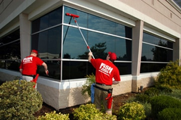 Two cleaners cleaning exterior windows of an office building