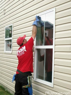 Window cleaner wiping down exterior residential window
